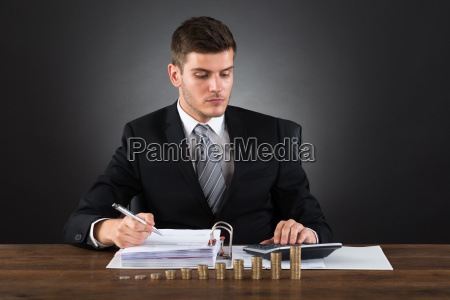 businessman calculating tax with coins at