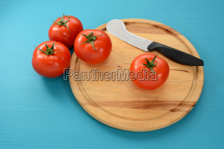 four tomatoes on a chopping board