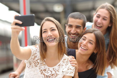 group of four friends taking selfie