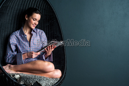 relaxed woman on bubble chair reading