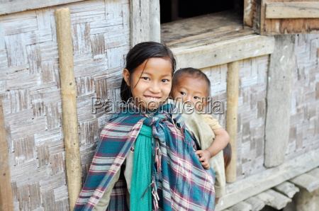 smiling older sister carrying kids in