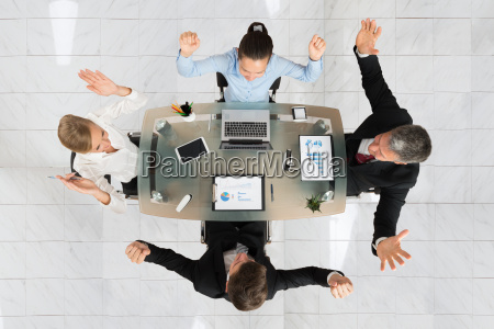 excited businesspeople sitting at desk