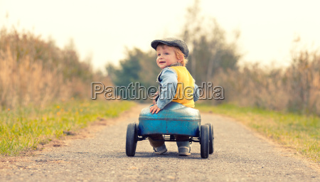 laughing boy with his pedal car