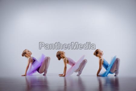 three little ballet girls sitting in