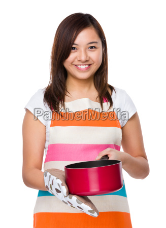 asian housewife using saucepan with oven