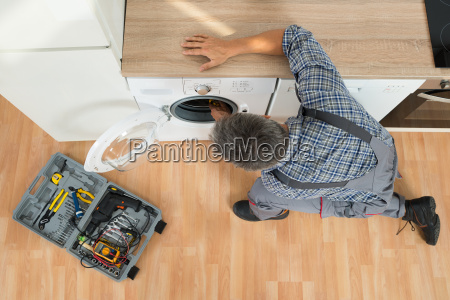 handyman checking washing machine at home