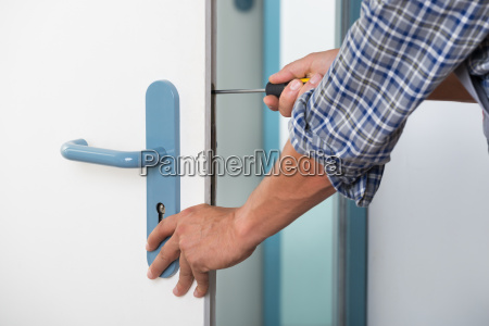 technician fixing lock in door with