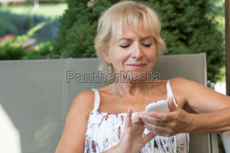 blonde senior woman with smart phone