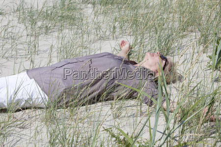 woman is lying in the dunes
