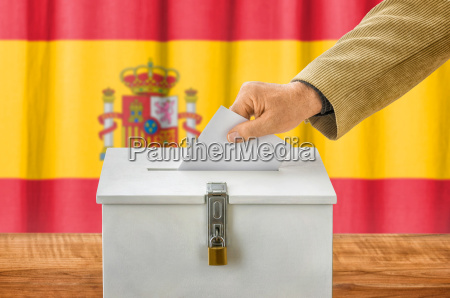 man throws ballot paper in electoral