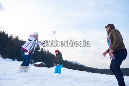 happy family playing together in snow