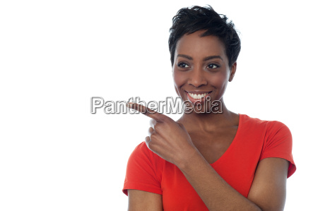 young smiling woman pointing away