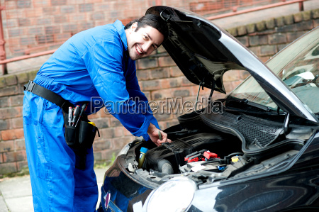 young mechanic inspecting car parts