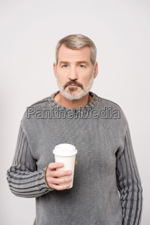 elderly man holding beverage