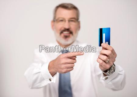 elderly man focusing on debit card