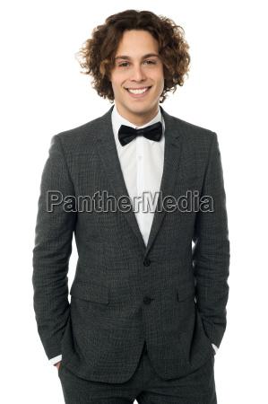 elegant man in tuxedo posing over