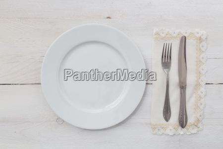 white plate and cutlery on light