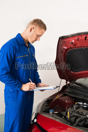 mechanic standing near car writing on