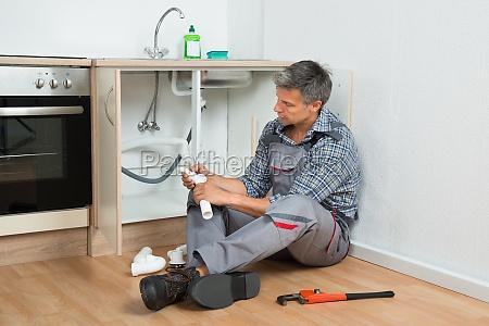 plumber repairing sink pipe in kitchen
