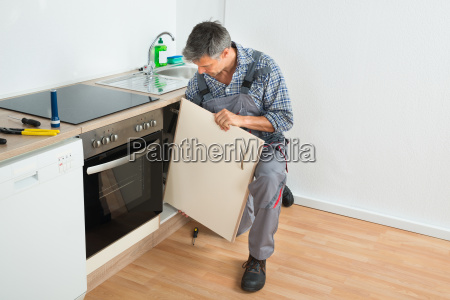 handyman fixing sink door in kitchen