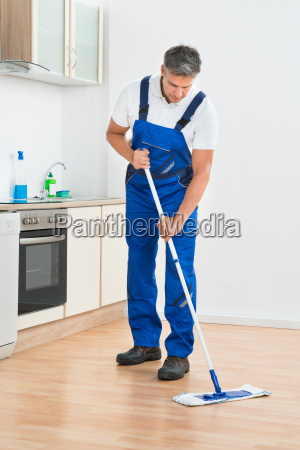 worker mopping floor in kitchen at