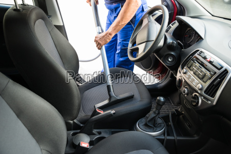 man vacuuming car seat with vacuum