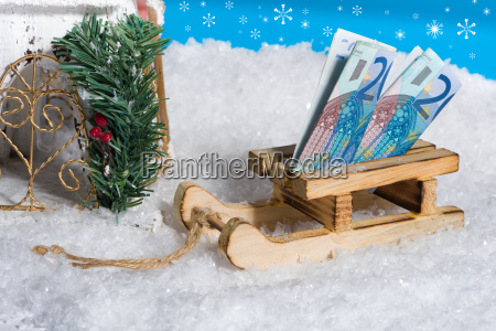 sledge on snow with money gift