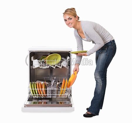 woman arranging utensils in dishwasher over
