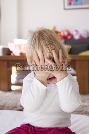baby hands covering her face
