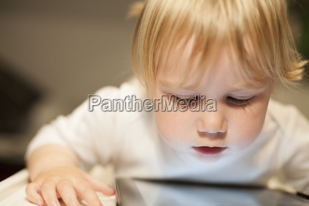 blonde baby looking at screen tablet