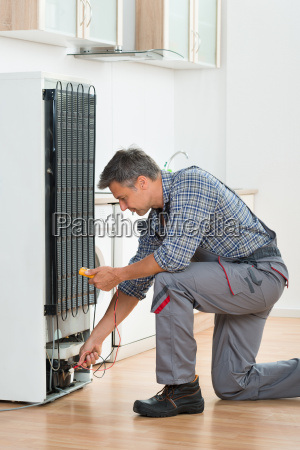 technician checking fridge with multimeter at