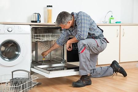 repairman repairing dishwasher with screwdriver in