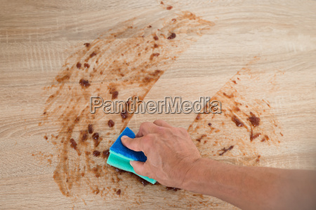 man cleaning kitchen counter with sponge