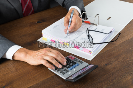 accountant checking invoice with calculator