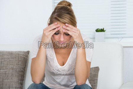 woman massaging head while suffering from