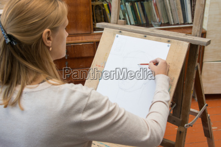 she paints on an easel in