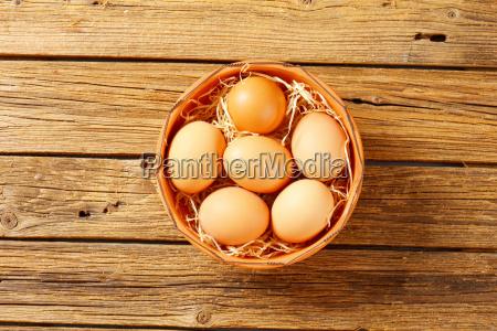 brown eggs in terracotta bowl
