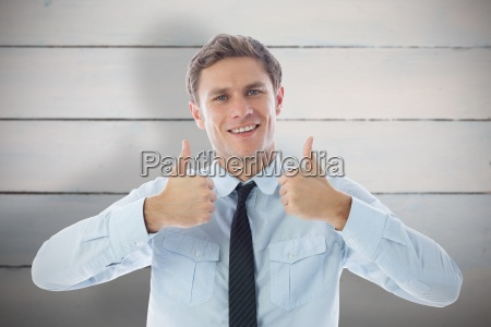 composite image of businessman showing thumbs