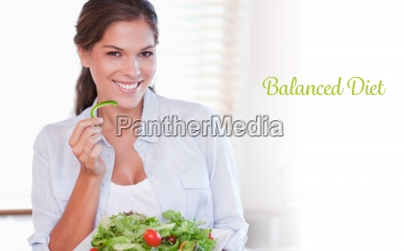 balanced diet against smiling woman eating