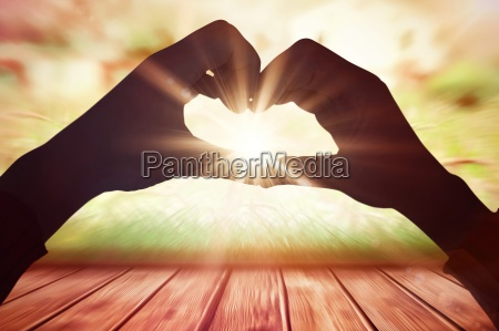composite image of woman making heart