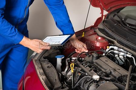 mechanic using digital tablet while examining