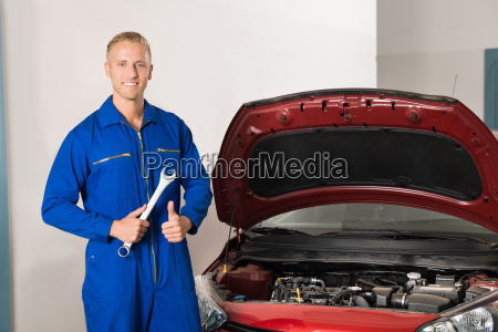 smiling mechanic standing in front of