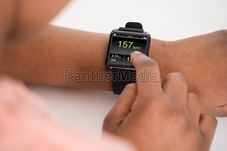 human hand wearing smartwatch showing heartbeat