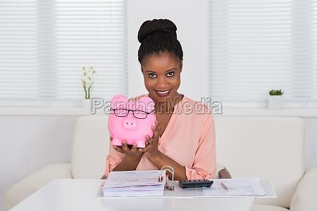 woman holding piggybank with eyeglasses