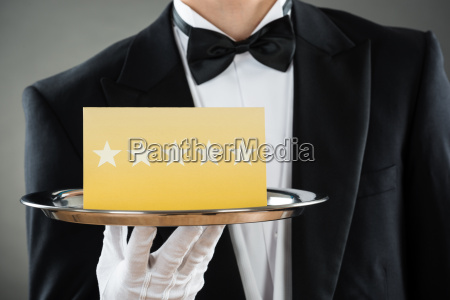 midsection of waiter holding tray with