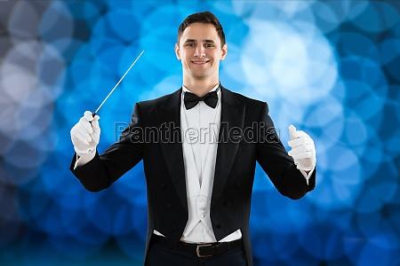 happy music conductor holding baton