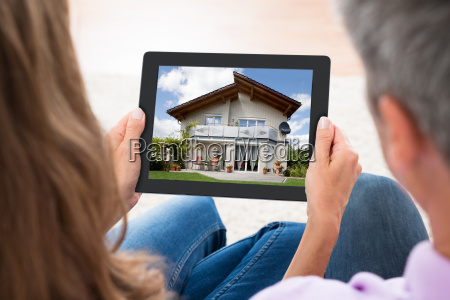 couple looking at house photo on