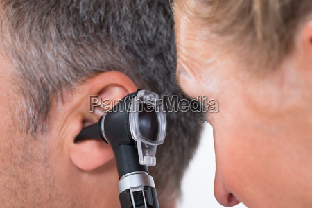 doctor examining patients ear