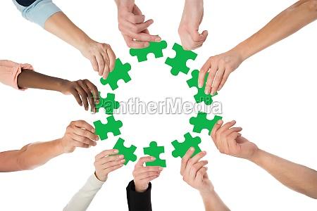creative business people holding green jigsaw