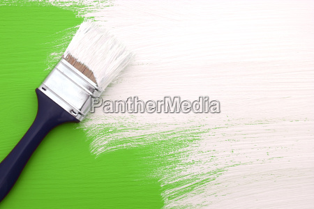 paintbrush with white paint painting over